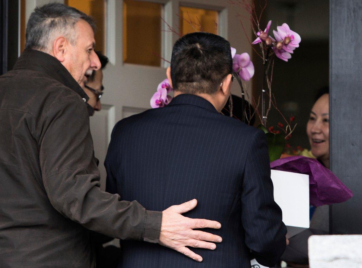 孟晚舟及康明凱在加拿大及中國大陸被捕,兩人遭受的待遇有著天壤之別,哪個政府在迫害人權一目瞭然。圖為去年12月12日,孟晚舟獲交保後隔天,在家中迎接來訪的中共領事官員。(Jason Redmond/AFP)
