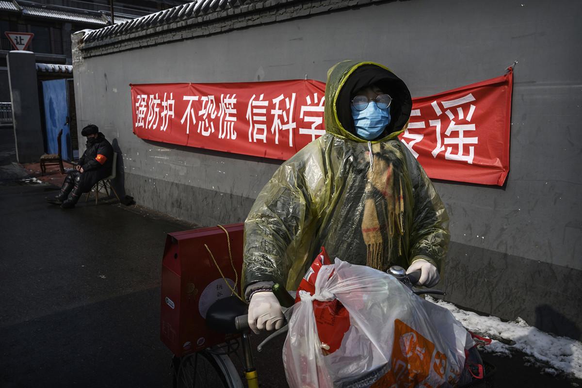 大陸中共病毒肆虐,中共唯恐民怨沸騰危及政權穩定。圖為2月7日北京街道上的一名婦女帶著購買的商品回家。(Getty Images)