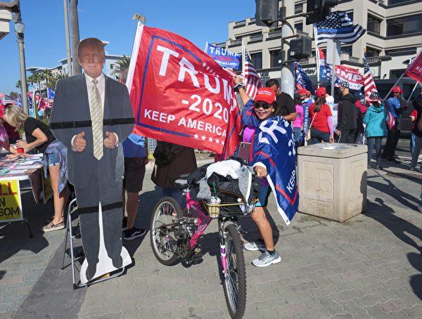 居民在杭廷頓海灘和特朗普總統像合照。(李梅/大紀元)