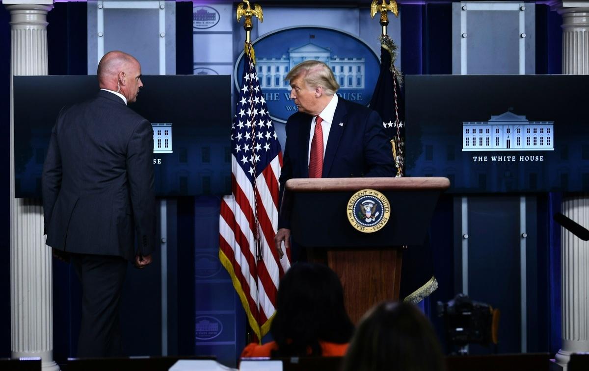 2020年8月10日,特勤局特工請川普離開白宮新聞會現場。(Brendan Smialowski/AFP)
