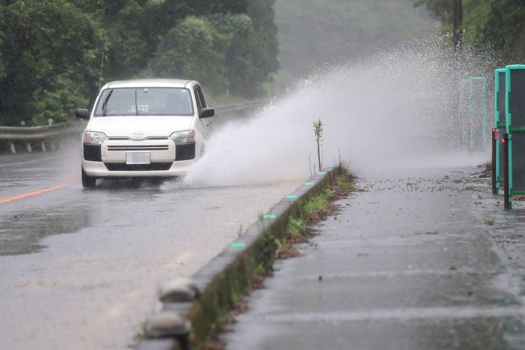 2019年7月3日,熊本縣蘆北町一輛汽車在雨中行駛。(JIJI PRESS/AFP/Getty Images)