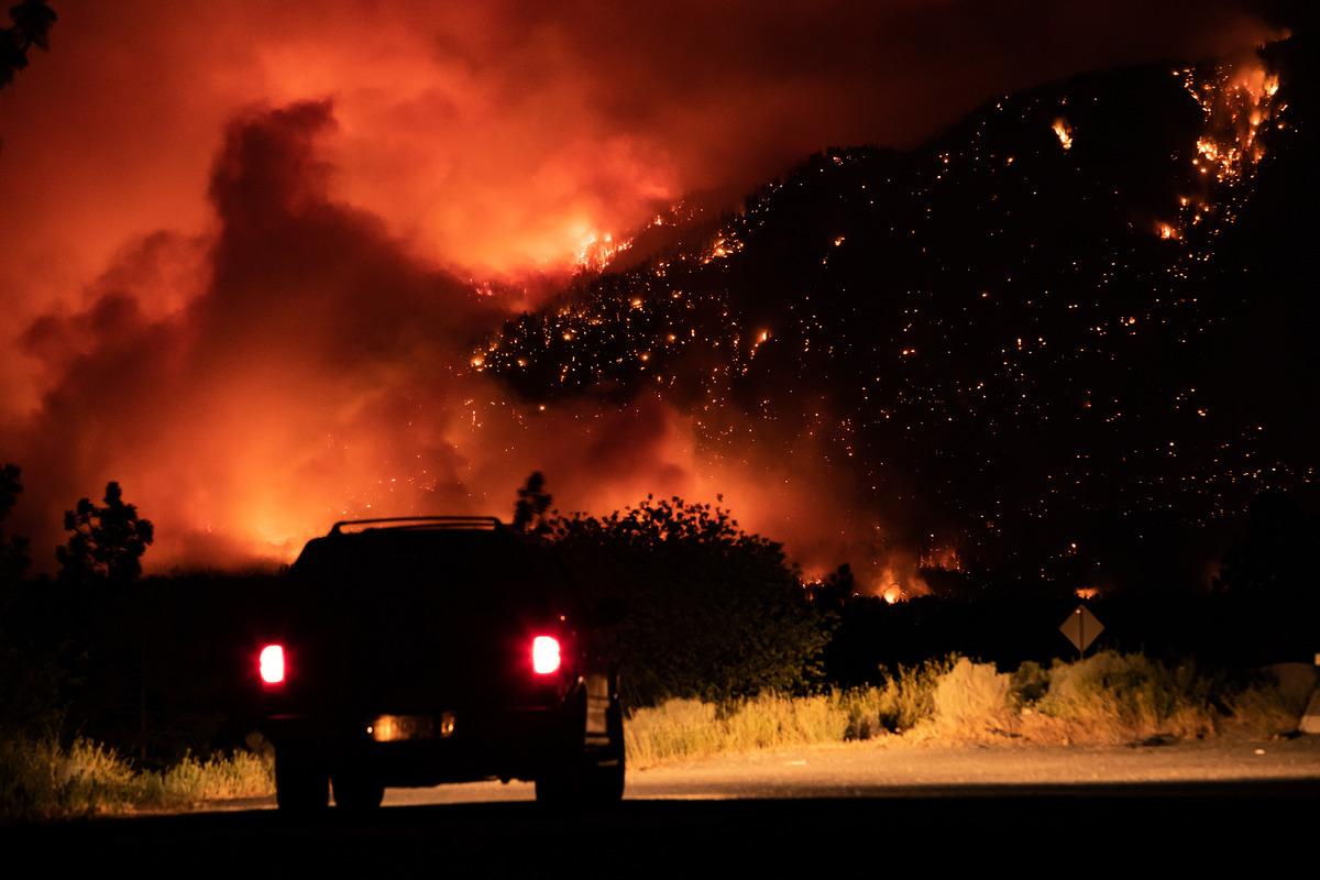 2021年7月1日,一名駕車者在加拿大橫貫公路的一個出口處看著山火在卑詩省利頓的山邊燃燒。(加通社)