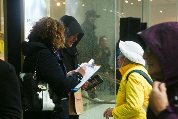 很多路人冒著風雨停下腳步,在徵簽板上簽字支持法輪功。(譚鑫/大紀元)