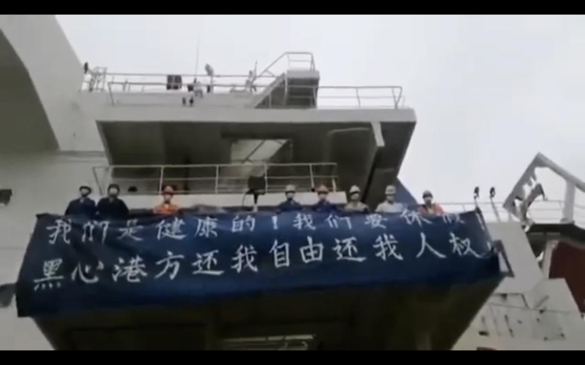 圖為2020年3月,中共病毒疫情期間,梁海斌和同事被困在船上,打橫幅抗議。(受訪者提供)