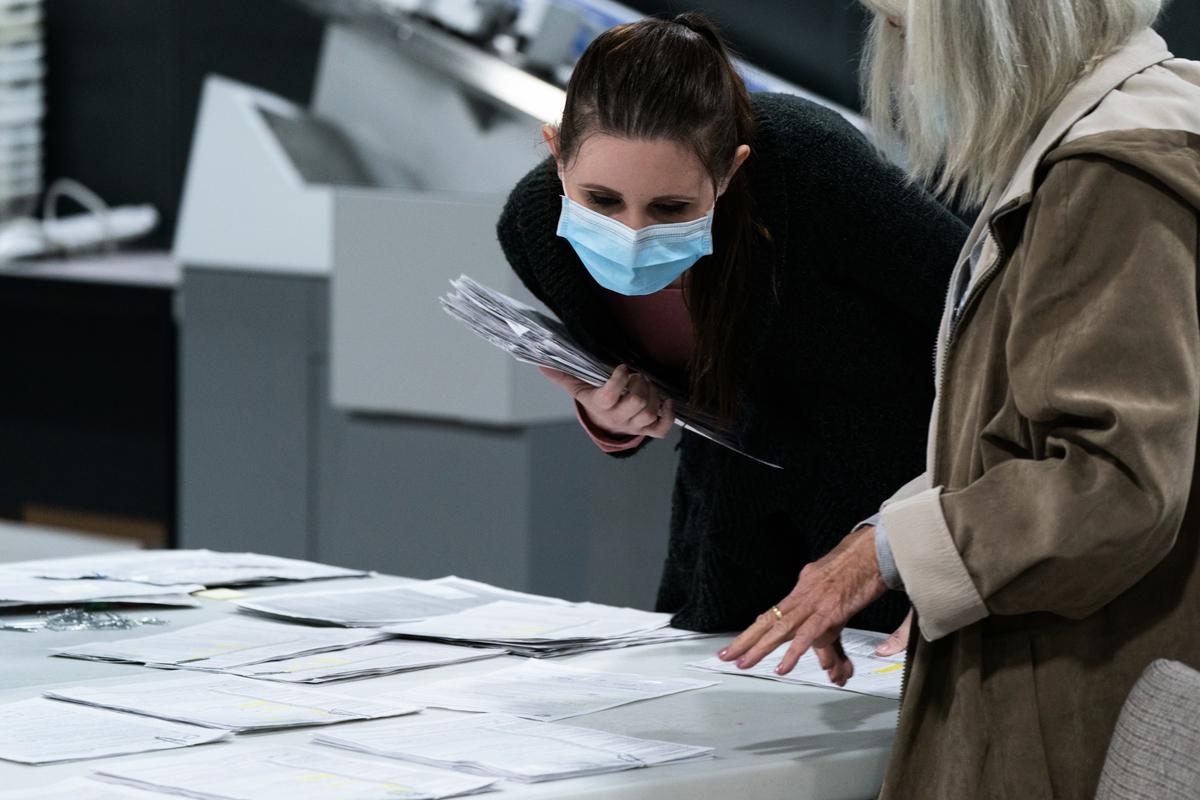 11月7日佐治亞州正將郵寄選票分類存放的選務人員。(Elijah Nouvelage/Getty Images)