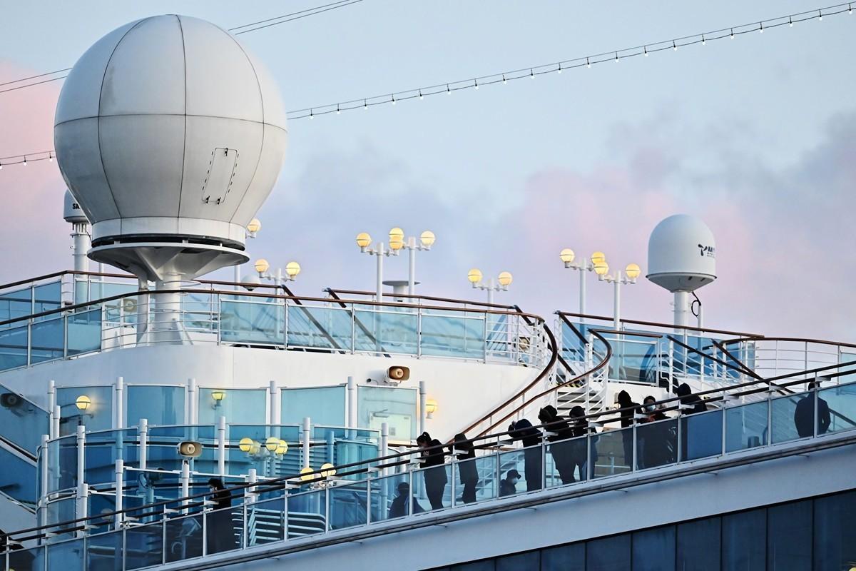 2020年2月18日,停靠在日本橫濱的「鑽石公主號」(Diamond Princess)郵輪上仍然處於隔離狀態的人們。(CHARLY TRIBALLEAU/AFP)