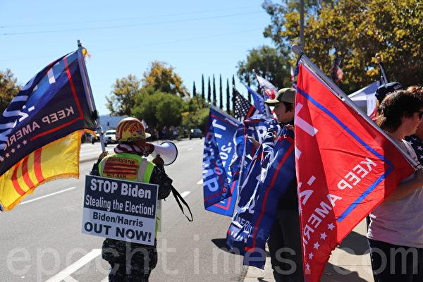 11月15日,聖地牙哥縣選民在波威市Pomerado大道邊聲援特朗普。一名抗議者身背寫著「阻止拜登竊選」「拜登/哈里斯出局」的標語(鄧舒語/大紀元)