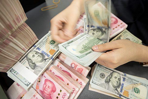 人民幣在3月27日對美元貶值,每美元對人民幣的離岸價格從周五早晨6時的7.0824元上漲至20時44分的7.1169元。(STR/AFP via Getty Images)