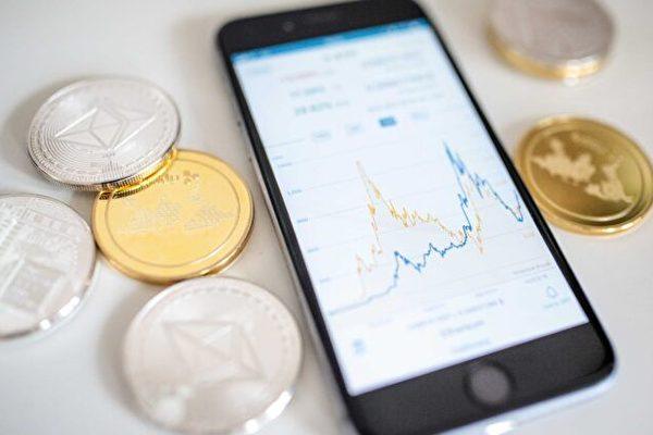 2018年4月25日,英國倫敦,萊特幣litecoin、瑞波幣ripple和以太加密貨幣ethereum cryptocurrency「山寨幣altcoins」位於智能手機旁,顯示以太幣當前的價格表。(Jack Taylor/Getty Images)