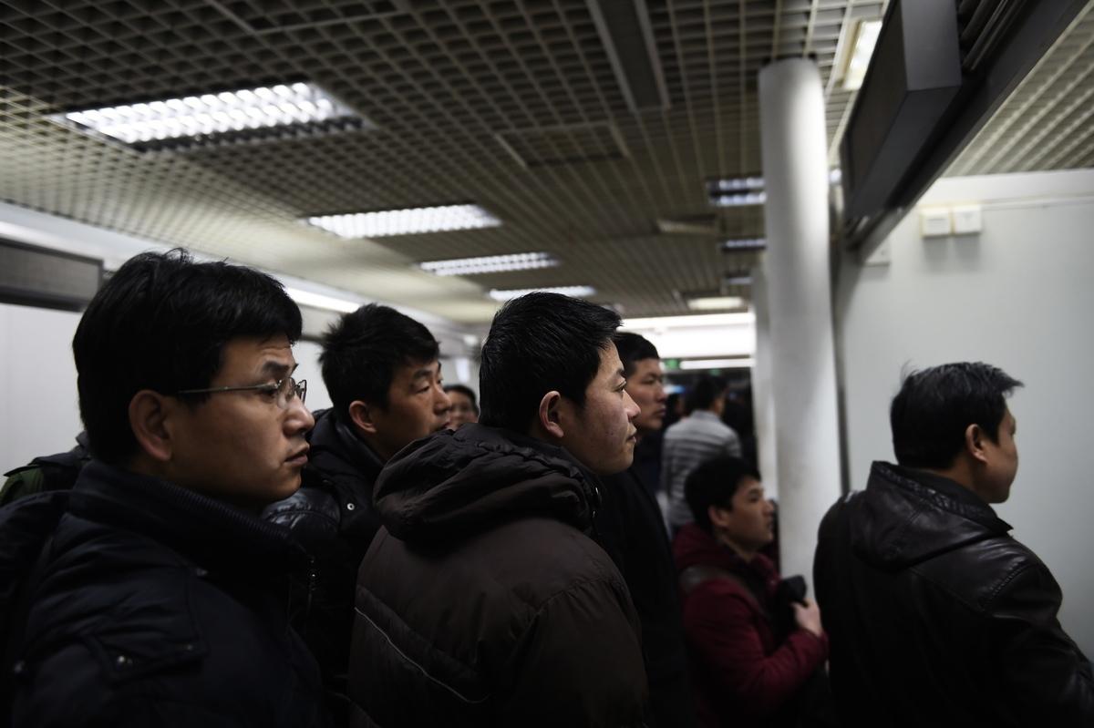 經濟下行,大陸高科技公司頻頻傳裁員。圖為北京一就業市場的找工的工人。(GREG BAKER / AFP)