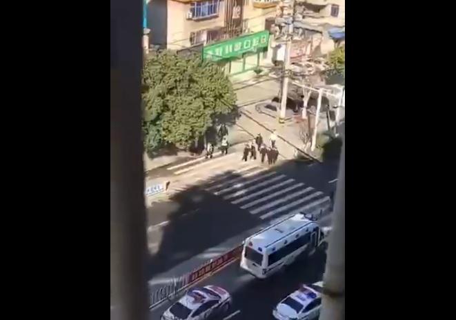 武漢市實施完全封閉管理首日,常青花園社區居民仍有在外散步活動者被巡邏警察強制送往體育館集中隔離。(影片截圖)