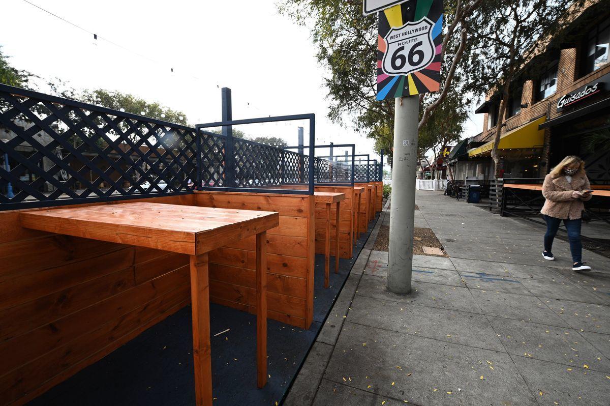 12月29日,加州宣佈將南加州以及中加一些地區的居家防疫令再次延長至少3周。圖為2020年11月23日,在加州西荷里活一家酒吧和餐廳外,一名女子從空蕩蕩的戶外用餐區走過。(ROBYN BECK/AFP via Getty Images)
