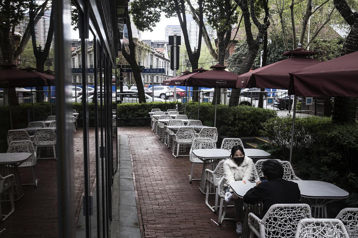 2020年4月1日,兩位武漢市民坐在一家空蕩盪的餐館外面。(Photo by Getty Images)