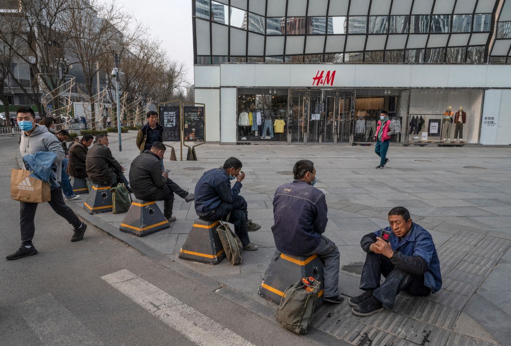 3月25,一群工人坐在服裝品牌H&M北京旗艦店外。中共煽動抵制包括H&M在內的西方主要品牌,最終傷害的還是中國經濟和老百姓的就業。(Kevin Frayer/Getty Images)