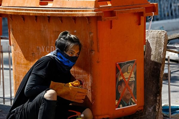 2021年3月8日,在仰光抗議軍事政變的活動中,一名抗議者躲在貼著緬甸武裝部隊首席高級將領閔昂‧拉林(Ang Ala Hlaing)肖像的垃圾桶後面。(STR/AFP via Getty Images)