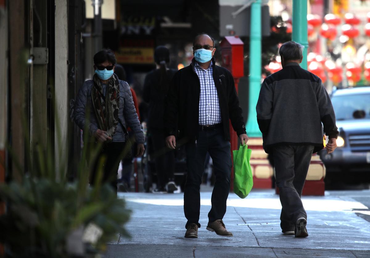 圖為帶著口罩在三藩市唐人街過往的行人。(Justin Sullivan/Getty Images)