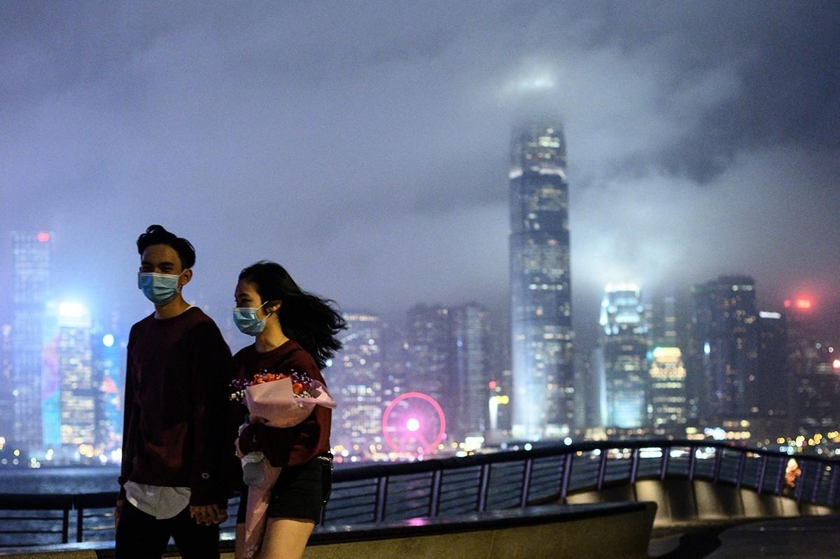 2020年2月14日,香港尖沙咀海濱長廊。一對年輕人戴著口罩以預防中共病毒(CCP Virus,俗稱COVID-19病毒)。(Photo by Philip FONG/AFP)