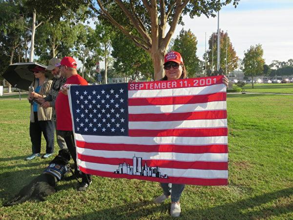 民眾舉著一面有2001.9.11字的美國國旗。(李梅/大紀元)