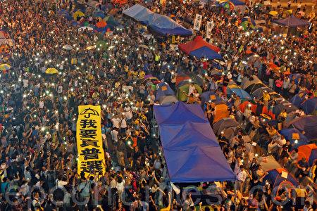 10月28日傍晚開始,逾萬香港人在金鐘雨傘廣場舉行「雨傘運動滿月紀念活動」,要求真普選,他們撐傘87秒回應警方在9月28日針對市民釋放了87個催淚彈。(潘在殊/大紀元)