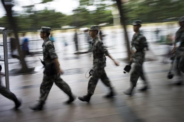 中共的五中全會召開之際,大陸國防部拋出國防部大學教授的文章,為在五中全會通報的軍改方案進行吹風。圖為在天安門廣場巡邏的軍人。(FRED DUFOUR/AFP/Getty Images)