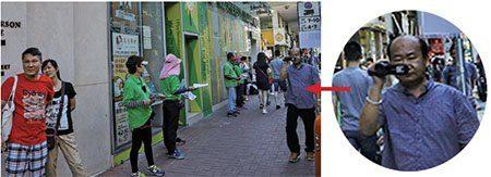 7月23日,青關會創會董事陳建華(圖中右,持攝錄機者)在指揮成員派發污衊單張及滋擾市民外,還拍攝成員的滋擾過程。(余鋼/大紀元)。