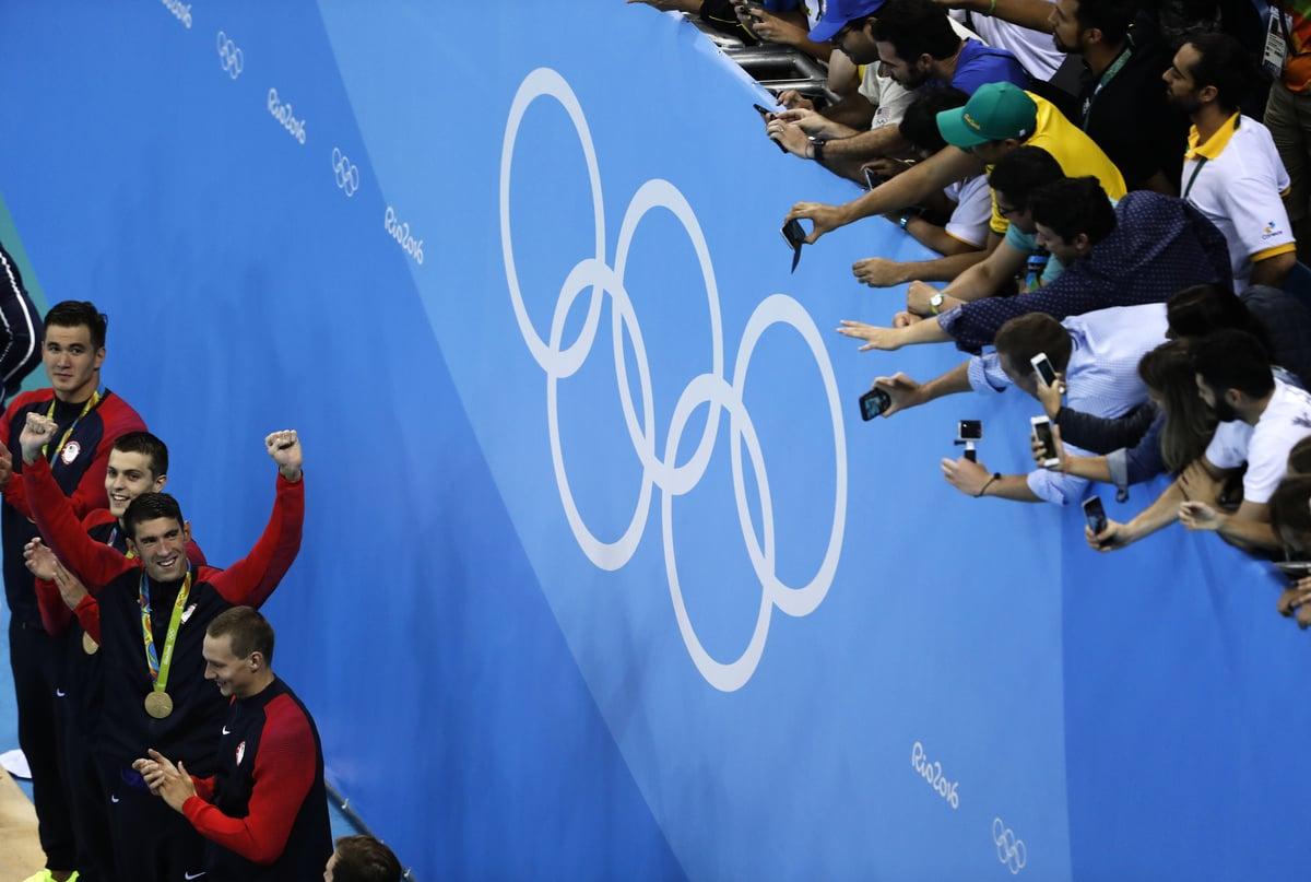 美國男泳將在菲比斯率領下,奪得了男子400米自由式接力賽金牌。圖為他們接受頒獎時,觀眾紛紛搶拍的畫面。(AFP PHOTO / Odd Andersen)