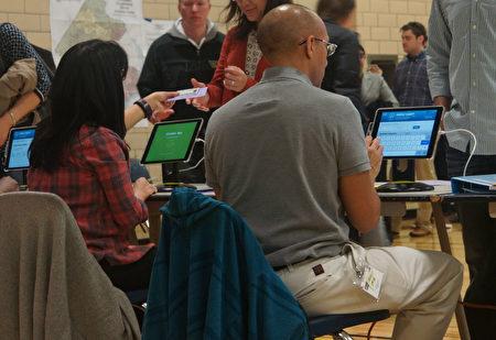 投票點的工作人員正在檢查選民的身份證件。(林樂予/大紀元)