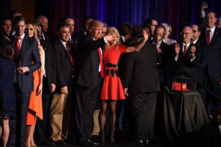 在勝選演講後合影時,特朗普以左手臂環抱康威的腰,在她向群眾揮手致意時,右手食指驕傲又感激地指著她。(TIMOTHY A. CLARY/AFP/Getty Images)