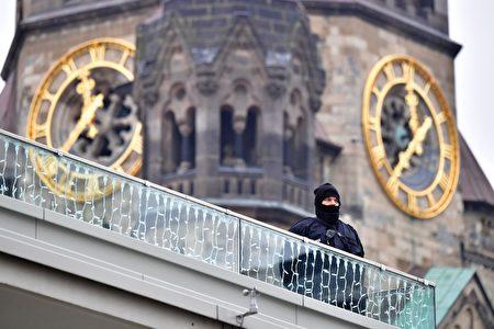 一名德國警察站在事發的聖誕市場附近,從高處監視下面的動靜。其背後是柏林紀念教堂。(ODD ANDERSEN /AFP/Getty Images)