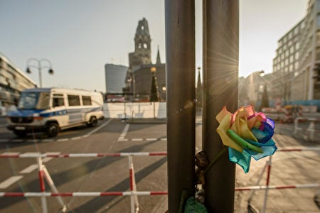 一朵七彩花別在兩個杆子之間,這裏離事發聖誕市場不遠。(CLEMENS BILAN/AFP)
