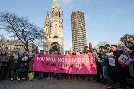 恐襲後兩天,在發生慘劇的聖誕市場旁,柏林市民和難民一起唱《四海一家》(We are the world)。橫幅上用英文寫著「我們不會分裂自己-我們都是柏林人」。(CLEMENS BILAN/AFP/Getty Images)