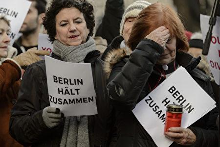 恐襲後兩天,在發生慘劇的聖誕市場旁,柏林市民和難民一起唱《四海一家》(We are the world)。圖為兩位柏林市民,其手中的紙上寫著「柏林團結起來」。(ODD ANDERSEN /AFP/Getty Images)