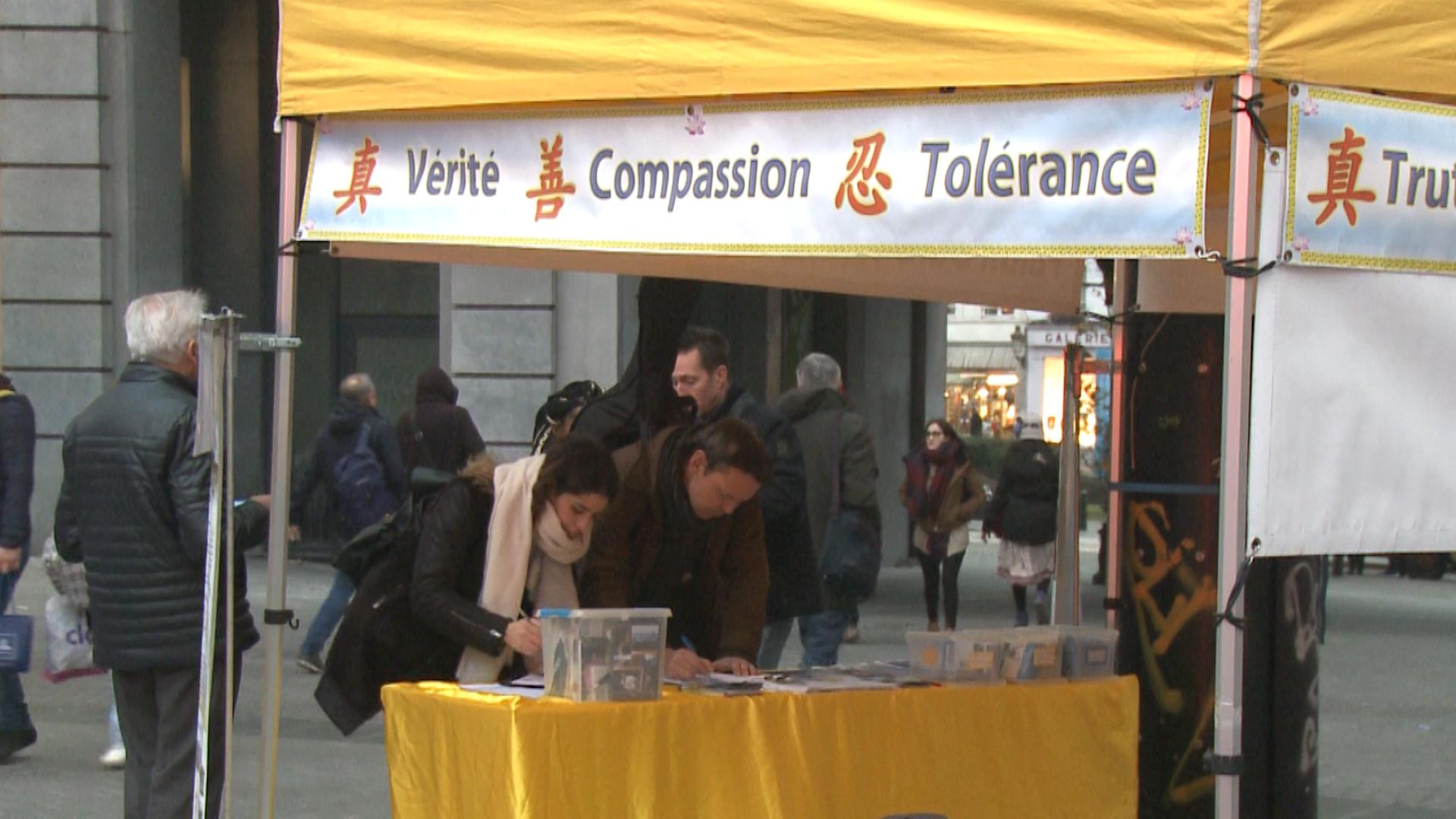 比利時民眾支持法輪功,在制止中共迫害法輪功的請願信上簽字 。(新唐人)