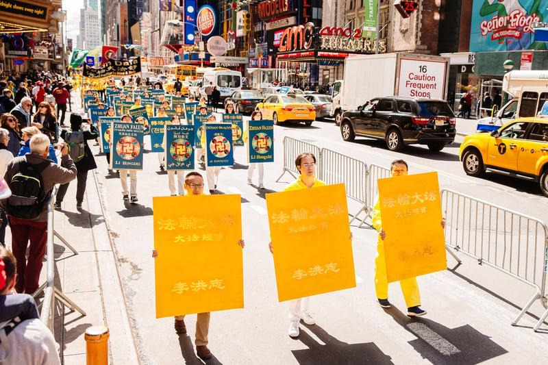 2017年5月12日,紐約上萬人舉行慶祝法輪大法弘傳世界25周年活動,並舉行橫貫曼哈頓中心42街的盛大遊行。圖為法輪功學員向民眾展示不同語種的《轉法輪》經書。(愛德華/大紀元)