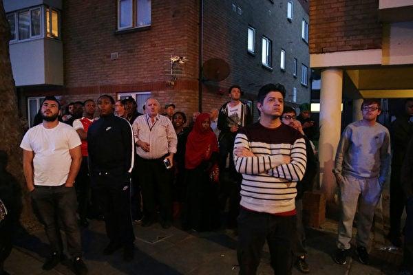 6月14日凌晨,倫敦24層的格倫費爾大廈發生大火,整棟公寓樓完全被大火吞噬。圖為圍觀的當地居民。(DANIEL LEAL-OLIVAS/AFP/Getty Images)