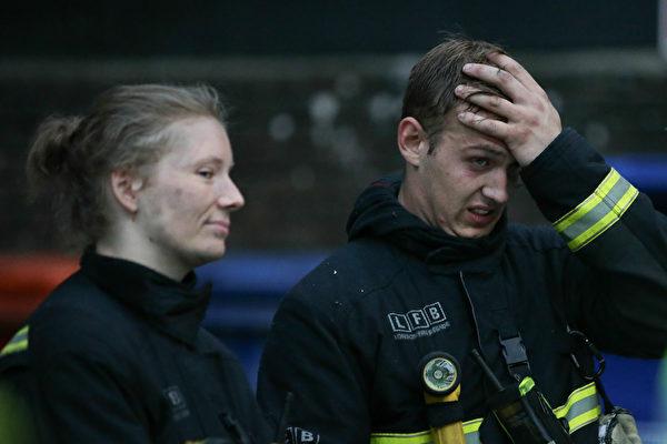 6月14日凌晨,倫敦24層的格倫費爾大廈發生大火,整棟公寓樓完全被大火吞噬。圖為消防員疲於滅火。(DANIEL LEAL-OLIVAS/AFP/Getty Images)