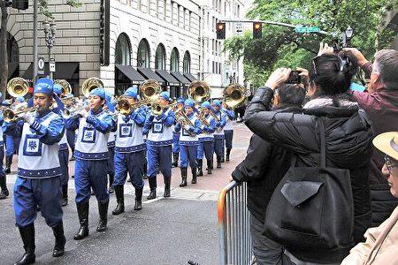 天國樂團在「玫瑰節大巡遊」一路演奏《法輪大法好》、《凱旋》、《神聖的歌》等原創樂曲,宏偉而平和的樂曲把法輪大法的美好帶給了這座美麗的城市。(明慧網)