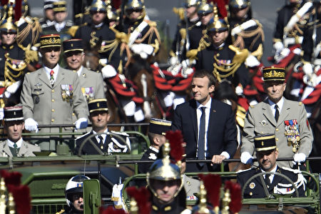 法國總統馬克龍在法軍總司令的陪同下乘車開導,穿越香榭麗舍大道,後面緊跟著的是騎兵儀仗隊。(ALAIN JOCARD/AFP/Getty Images)