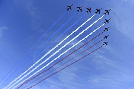法國巡邏兵飛行表演隊(Patrouille de France)的9架阿爾法教練機(Alpha Jet)飛越協和廣場閱兵主席台上空,尾部噴灑出藍白紅法國國旗三色煙霧。(SAUL LOEB/AFP/Getty Images)