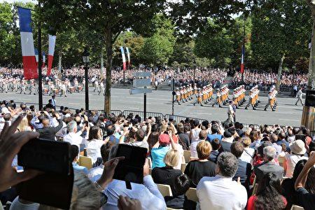香榭麗舍大道邊坐滿地觀禮民眾。(LUDOVIC MARIN/AFP/Getty Images)