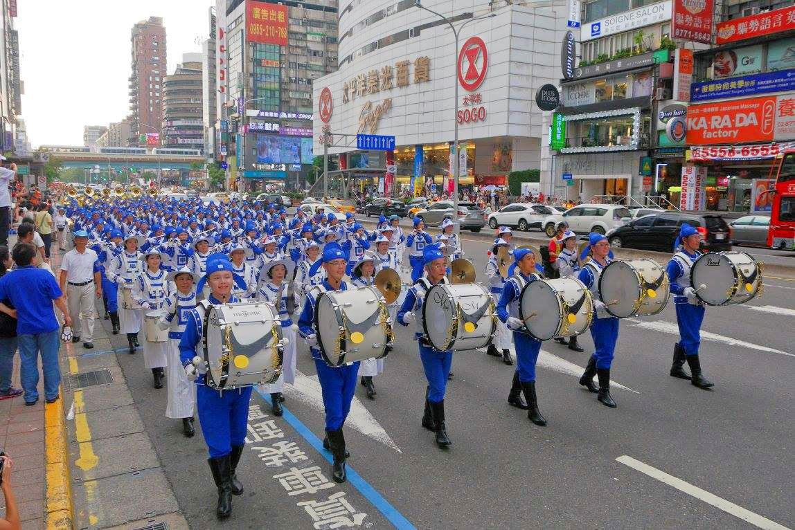 由法輪功學員組成的天國樂團參加台北世大運的嘉年華踩街遊行,精神抖擻地行經在台北市熱鬧的街頭。(明慧網)