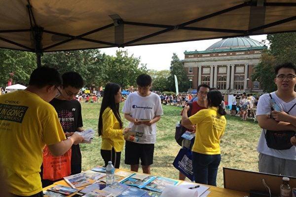 在伊大香檳分校社團招新活動上,身穿黃色衣服的法輪功學員向中國留學生講述真相。(明慧網)