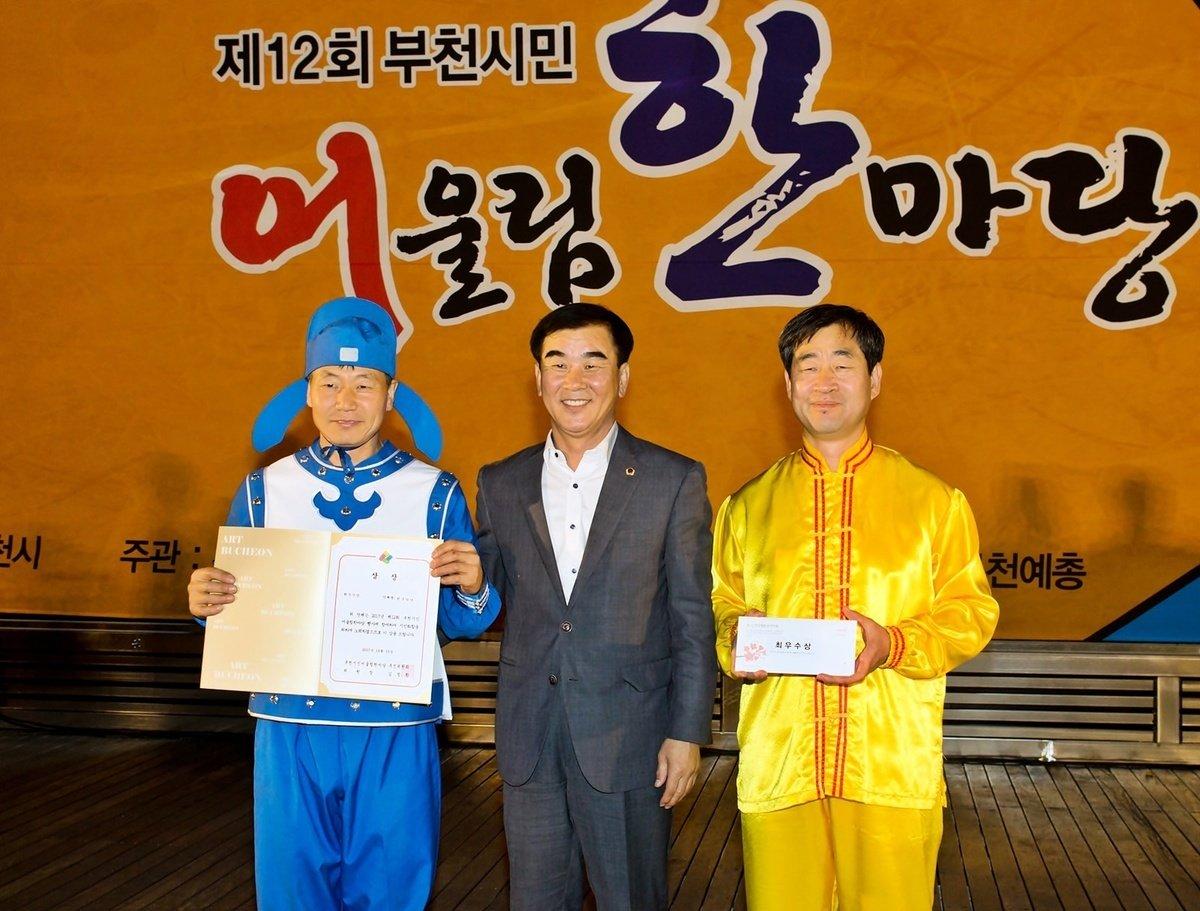 南韓京畿道議會文化觀光委員長(中),給參加此次慶典活動獲一等獎的法輪功團體頒獎。(金國煥/大紀元)