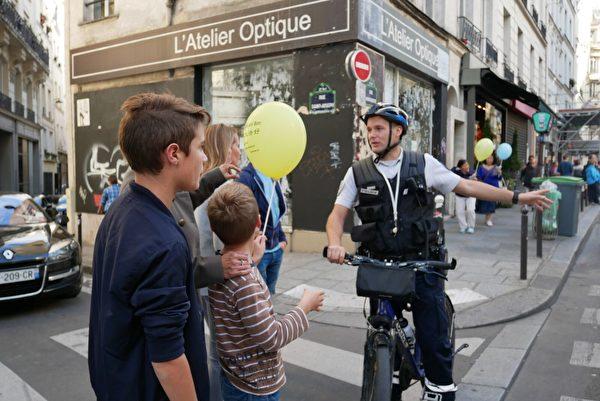 巴黎警察在給路人解釋法輪功遊行的目的。(張妮/大紀元)