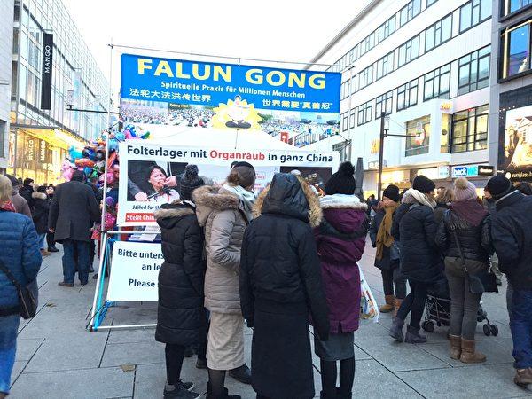 12月9日,人們在法輪功學員搭建的展板前駐足觀看法輪功真相。(羅瓊/大紀元)