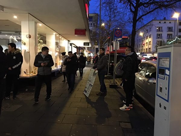 12月9日徬晚,法輪功學員Gianluca 在柏林大道旁給中國遊客看真相展板。(羅瓊/大紀元)