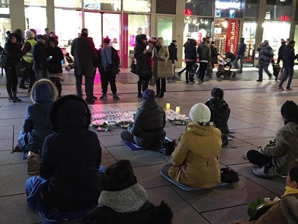 12月9日晚,人們來到法輪功學員舉辦的燭光守夜活動現場了解法輪功真相。(羅瓊/大紀元)