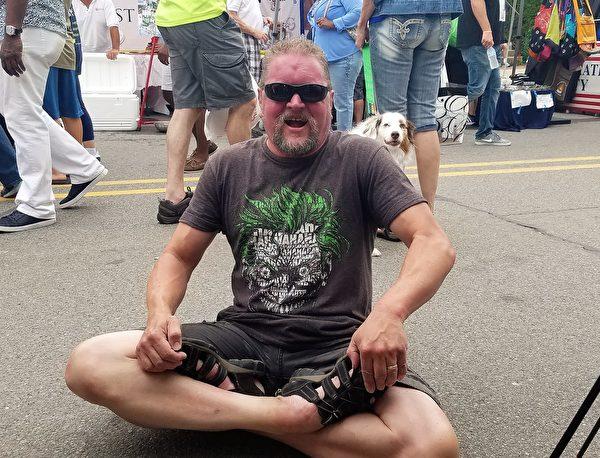 這位「紅面壯漢」仔細看了展板上的打坐照片,席地而坐,用手把雙腳搬起來做了個雙盤腿的動作,並自豪地喊道:「我從來沒有練過瑜伽,但我可以做這個(雙盤)!(I can do this.)」(尹婉/大紀元)