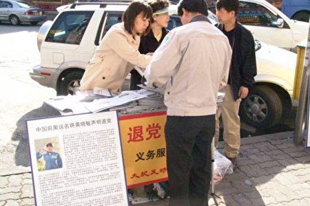 黃曉敏(左)在退黨服務站義務為大家服務。(大紀元)