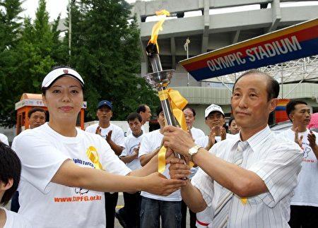 2007年7月2日下午3點,黃曉敏(左)手持火炬。(大紀元)